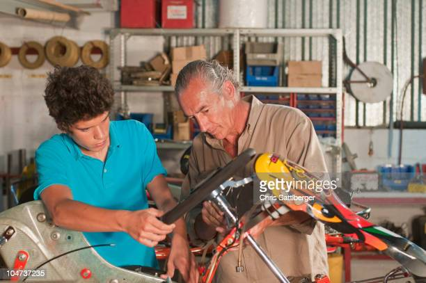 Hispanic grandfather and grandson working on go-cart