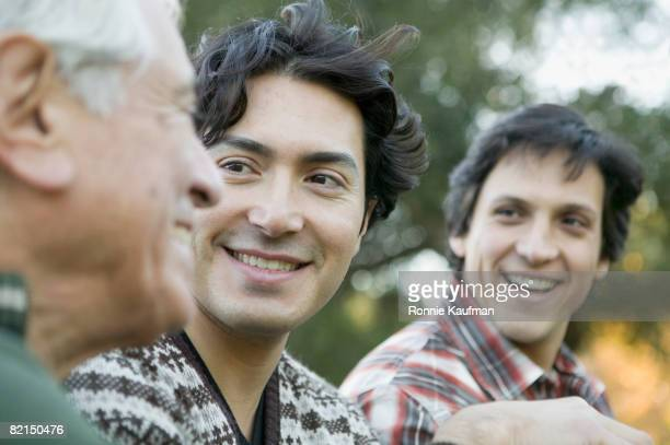 Hispanic grandfather and grandsons laughing outdoors