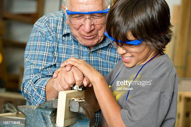 Hispanic grandfather and son planing wood in workshop
