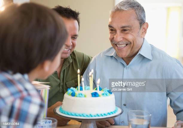 Hispanic grandfather, father and son celebrating birthday
