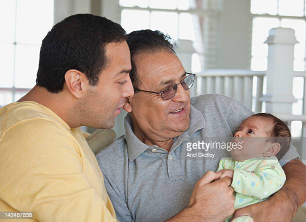 Hispanic grandfather holding baby girl