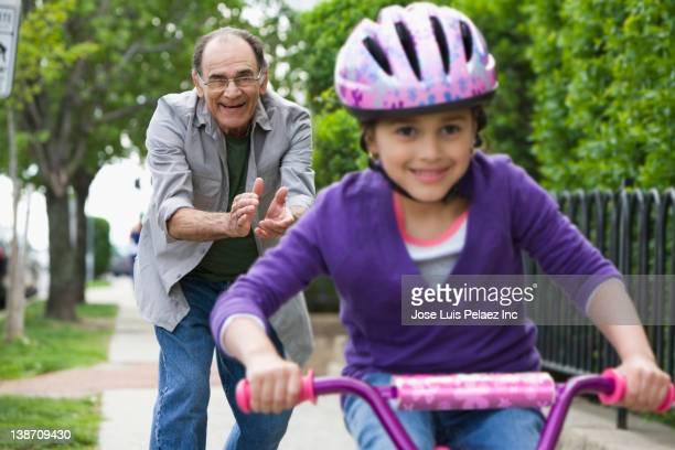 Hispanic grandfather teaching granddaughter to ride bicycle