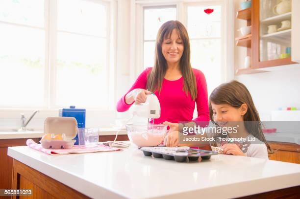 Hispanic grandmother and granddaughter baking in kitchen
