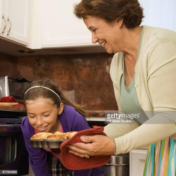 Hispanic grandmother and granddaughter baking muffins