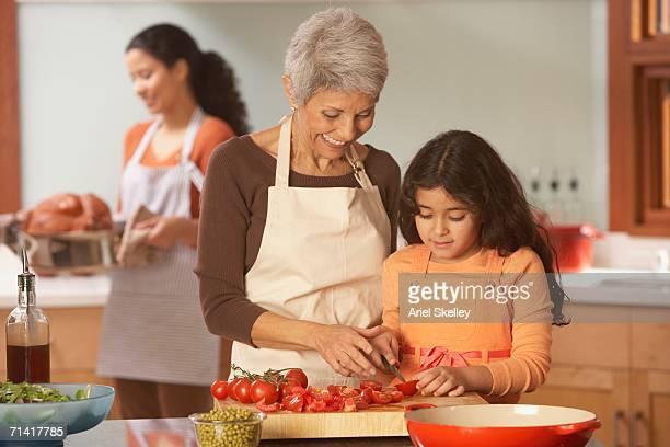hispanic grandmother and granddaughter cutting tomatoes in the kitchen - cortando preparando comida - fotografias e filmes do acervo