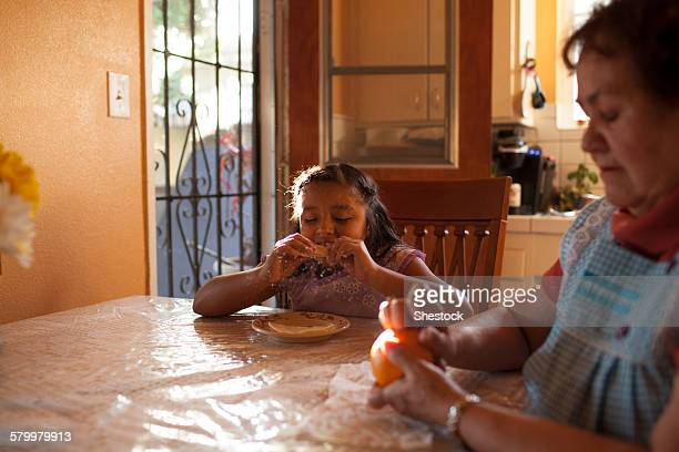 Hispanic grandmother and granddaughter eating in kitchen