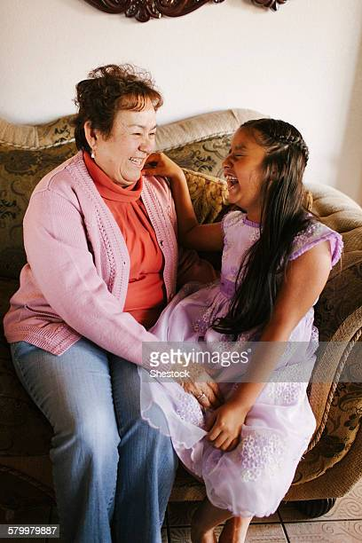 hispanic grandmother and granddaughter laughing on sofa - chubby granny stock pictures, royalty-free photos & images