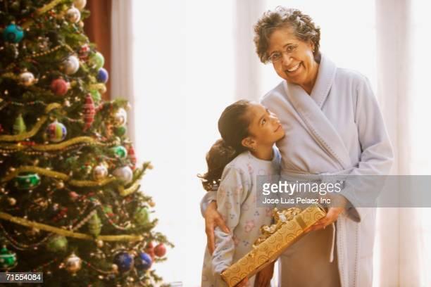 Hispanic grandmother and granddaughter on Christmas morning