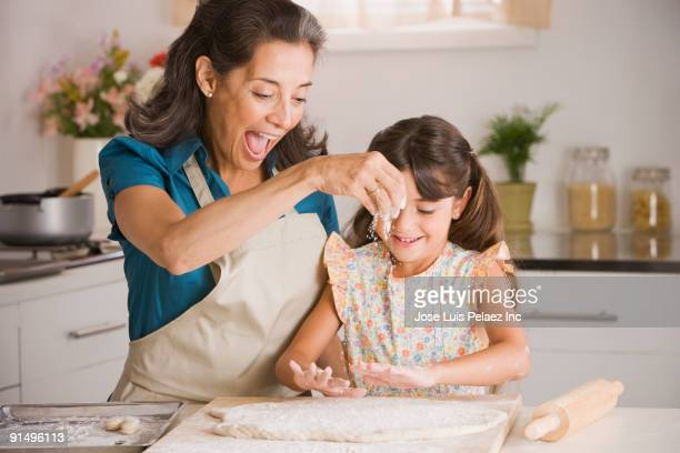 hispanic grandmother and granddaughter preparing dough - generation gap stock pictures, royalty-free photos & images