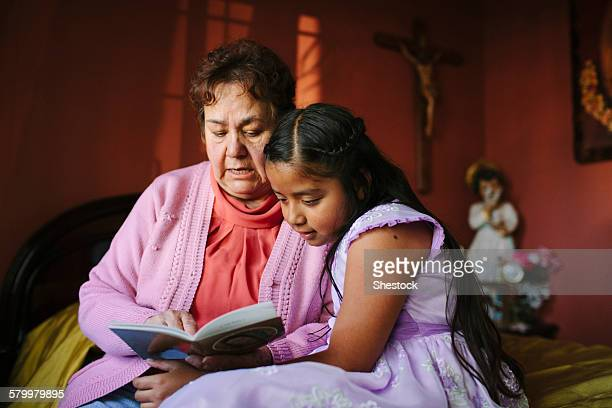 Hispanic grandmother and granddaughter reading book on bed