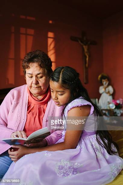 Hispanic grandmother and granddaughter ready book on bed
