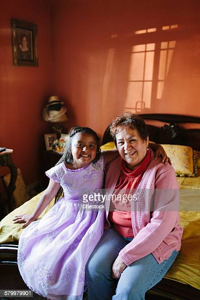Hispanic grandmother and granddaughter sitting on bed