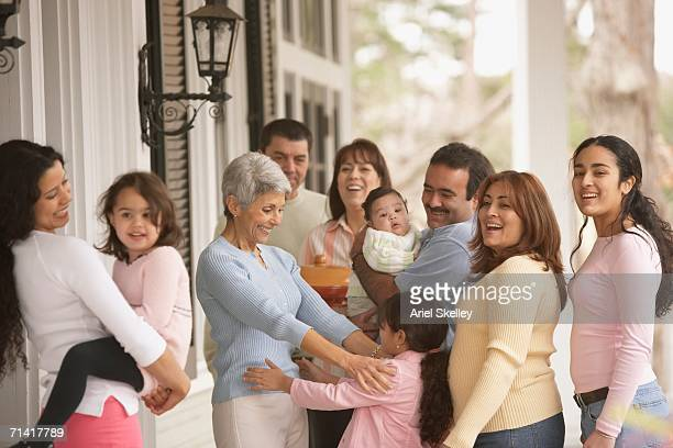 Hispanic grandmother hugging her granddaughter with family around