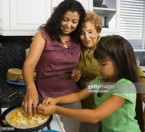 Hispanic grandmother, mother and daughter preparing food in kitchen