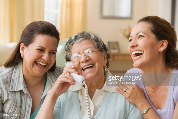 Hispanic grandmother, mother and daughter with telephone