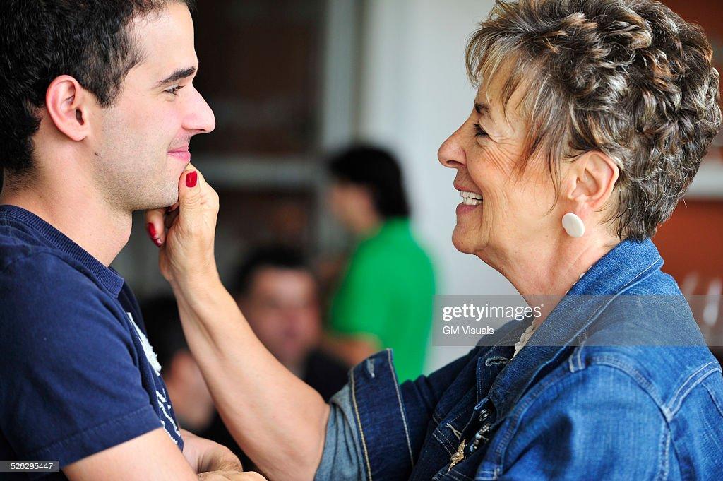 Hispanic grandmother pinching grandsons face : Stock Photo