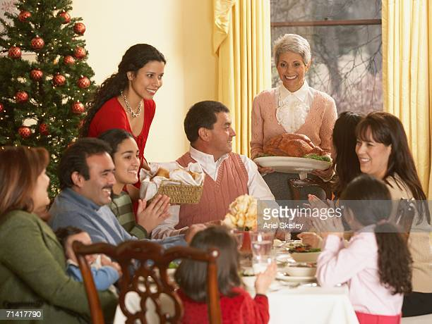 Hispanic Grandmother Presenting Turkey To Her Family At Christmas Dinner