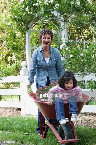 hispanic grandmother pushing granddaughter in wheelbarrow - jardinier humour photos et images de collection
