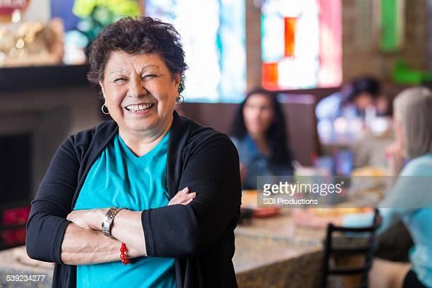 Grand-mère hispanique souriant dans la salle à manger du restaurant familial