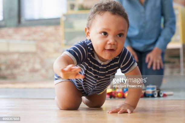 hispanic grandmother watching baby grandson crawling on floor - de quatro imagens e fotografias de stock