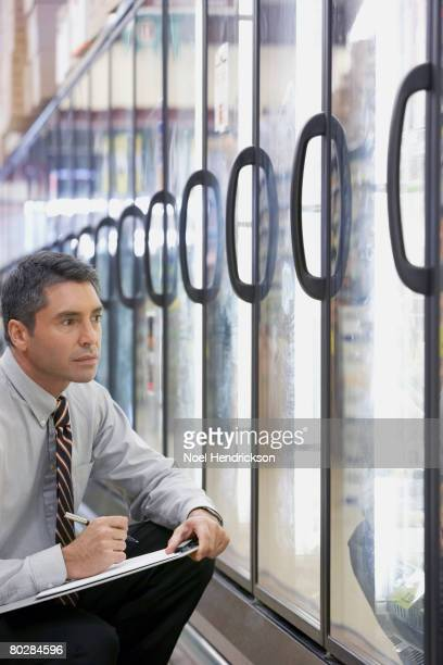 Hispanic grocery store manager writing on clipboard