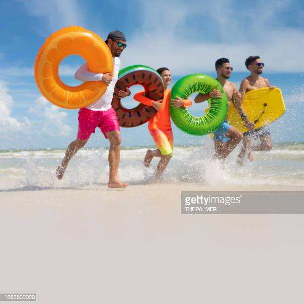 hispanic guys with inflatable ring tubes on a beach in miami - gulf coast states stock pictures, royalty-free photos & images