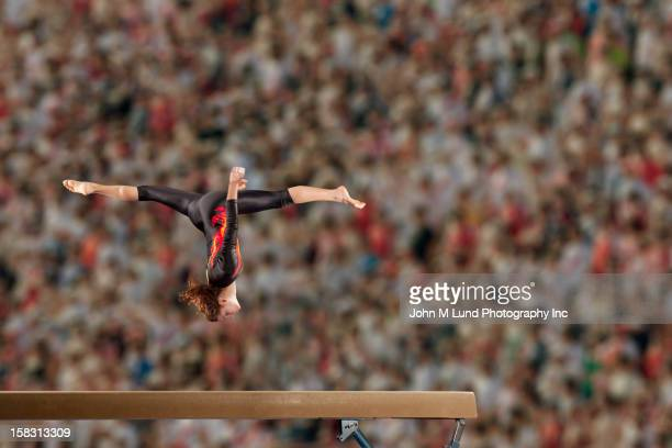 hispanic gymnast in mid-air over balance beam - gymnastique sportive photos et images de collection