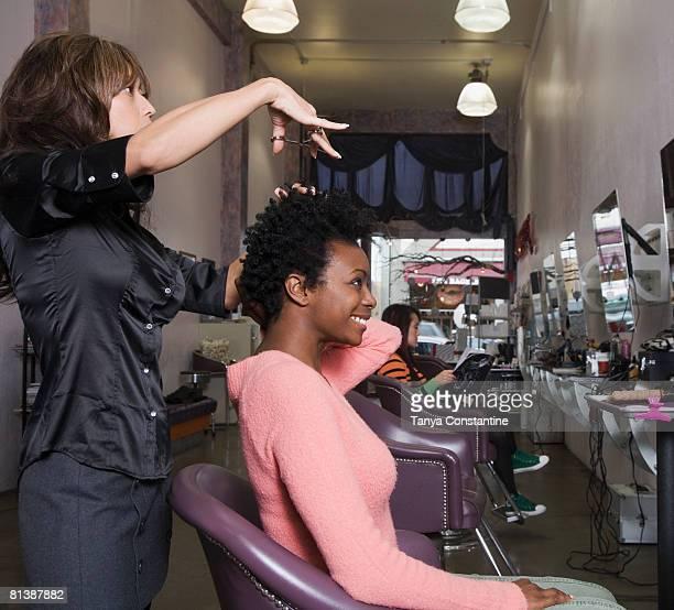 Hispanic hair stylist cutting African woman?s hair