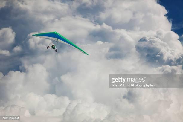 Hispanic hang glider flying through clouds