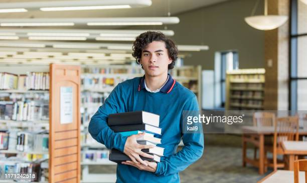 hispanic high school student carrying stack of books - one teenage boy only stock pictures, royalty-free photos & images