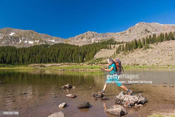 Hispanic hiker climbing on rocks in lake