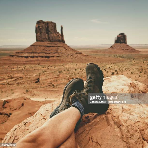Hispanic hiker resting boots on rock formation