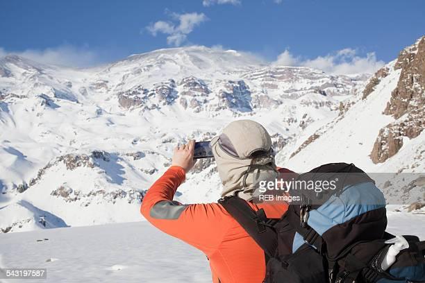 Hispanic hiker taking photograph of snowy mountain range
