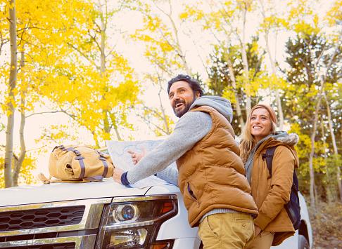 Hispanic hikers leaning on car hood reading map - gettyimageskorea