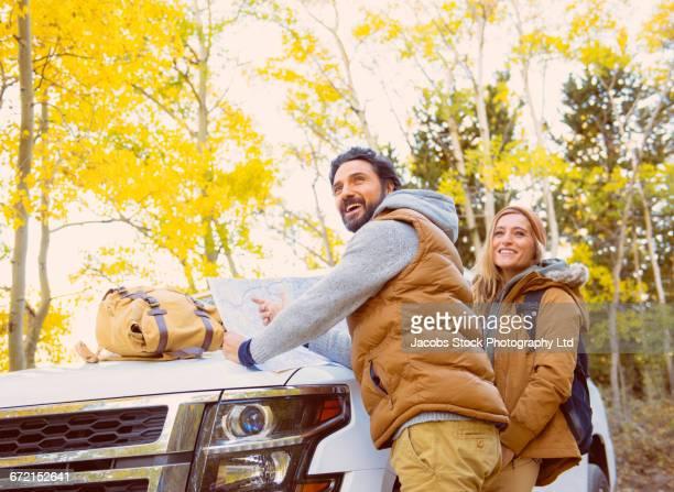 hispanic hikers leaning on car hood reading map - ärmellos stock-fotos und bilder
