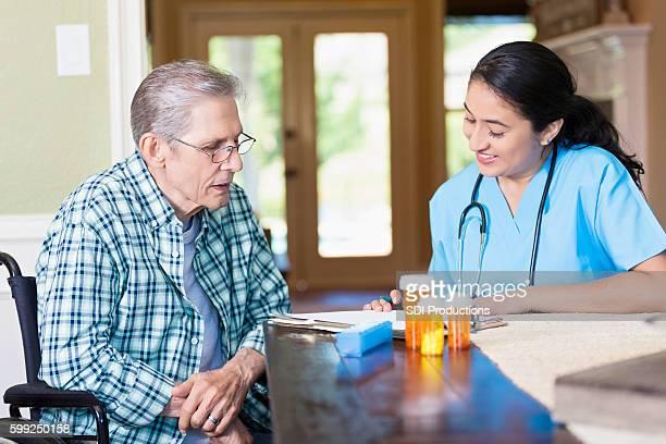 Hispanic Home health care nurse talks with enior patient