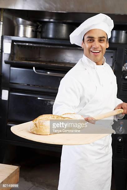 Hispanic male baker holding fresh bread