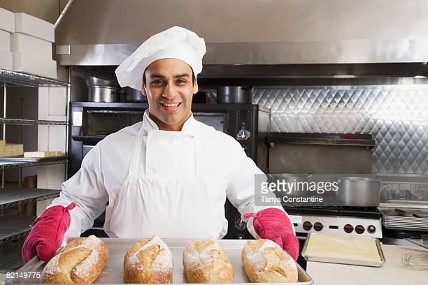 hispanic male baker holding tray of fresh bread - tanya constantine stock pictures, royalty-free photos & images