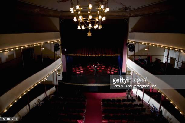 Hispanic male conductor in empty theater
