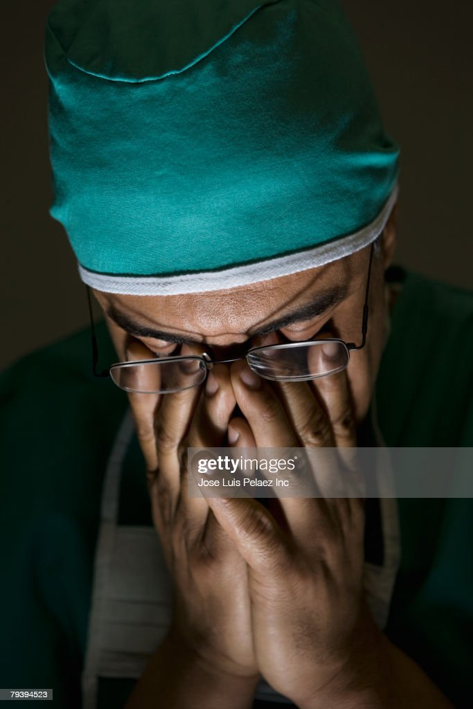 Hispanic male doctor with head in hands : Stock Photo