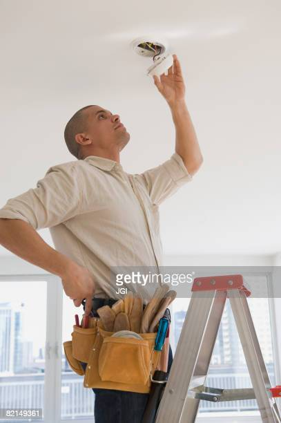 Hispanic male electrician fixing looking at wiring