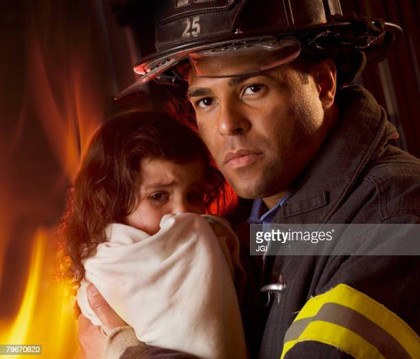 Hispanic male firefighter holding child