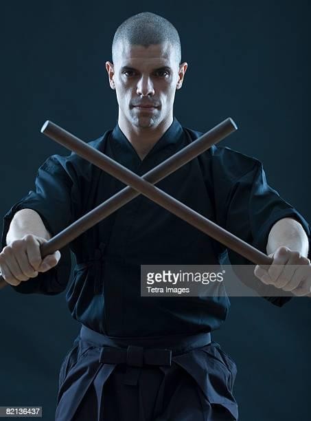 Hispanic male holding sticks in fighting stance