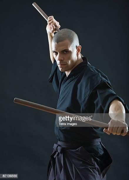 hispanic male holding sticks in fighting stance - 武道 ストックフォトと画像