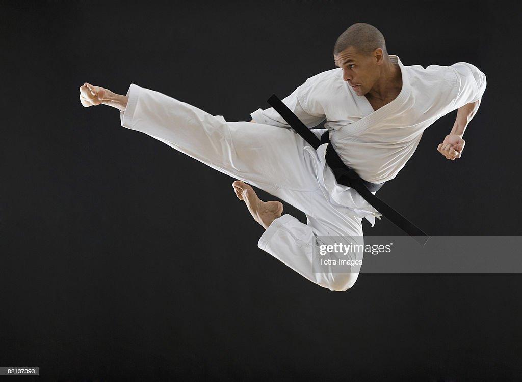 Hispanic male karate black belt kicking in air : Stock Photo