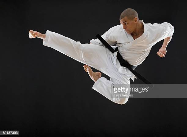Hispanic male karate black belt kicking in air