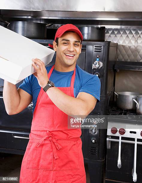 Hispanic male pizza maker holding box