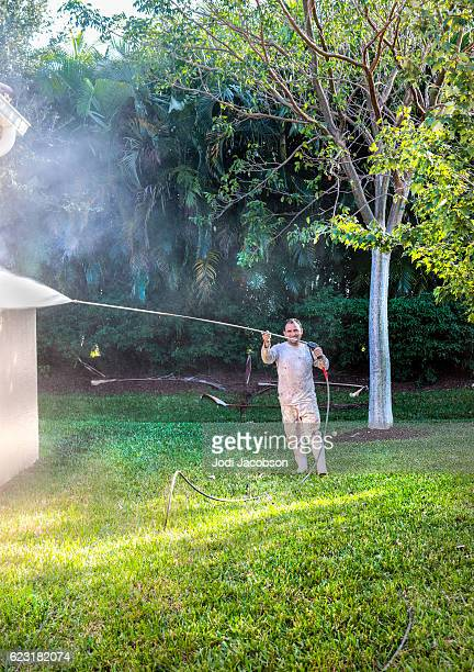 Hispanic Male power washing an upscale home