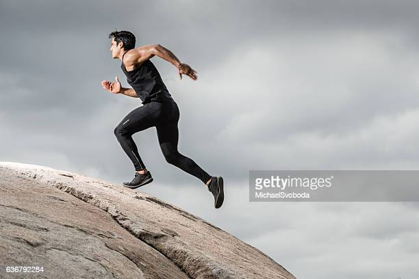 Hispanic Male Running Up A Granite Boulder In The Mountains