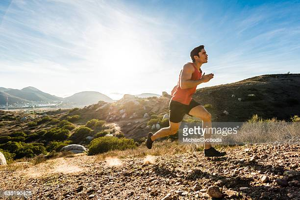 Hispanic Male Running Up A Steep Hill In The Mountains